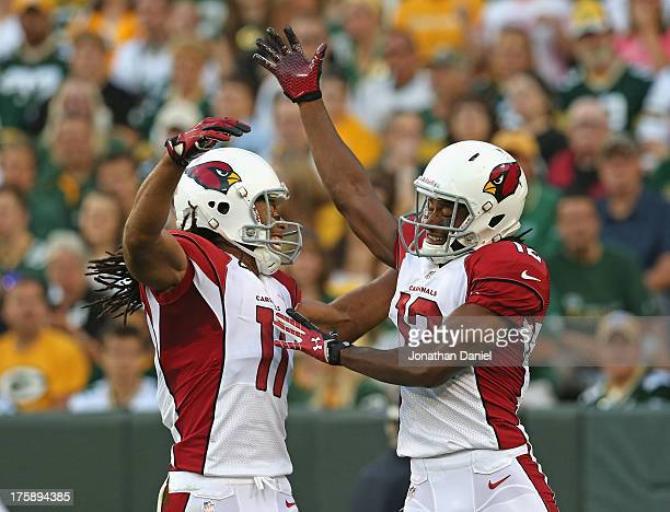 Andre Roberts of the Arizona Cardinals celebrates a touchdown catch with Larry Fitzgerald against the Green Bay Packers at Lambeau Field on August 9...