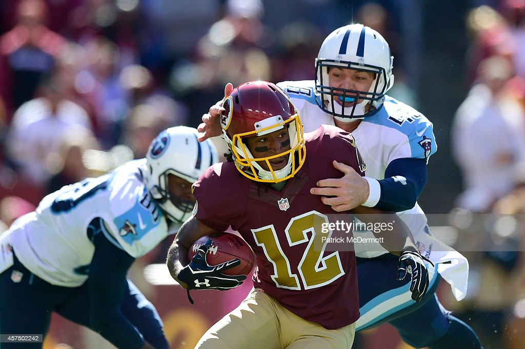 Andre Roberts #12 of the Washington Redskins is tackled by Beau Brinkley #48 of the Tennessee Titans during second quarter of their game at FedEx Field on October 19, 2014 in Landover, Maryland.