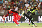 Andre Russell of the Thunder slides in to avoid a runout as Peter Nevill of the Renegades fields during the Big Bash League match between the Sydney...