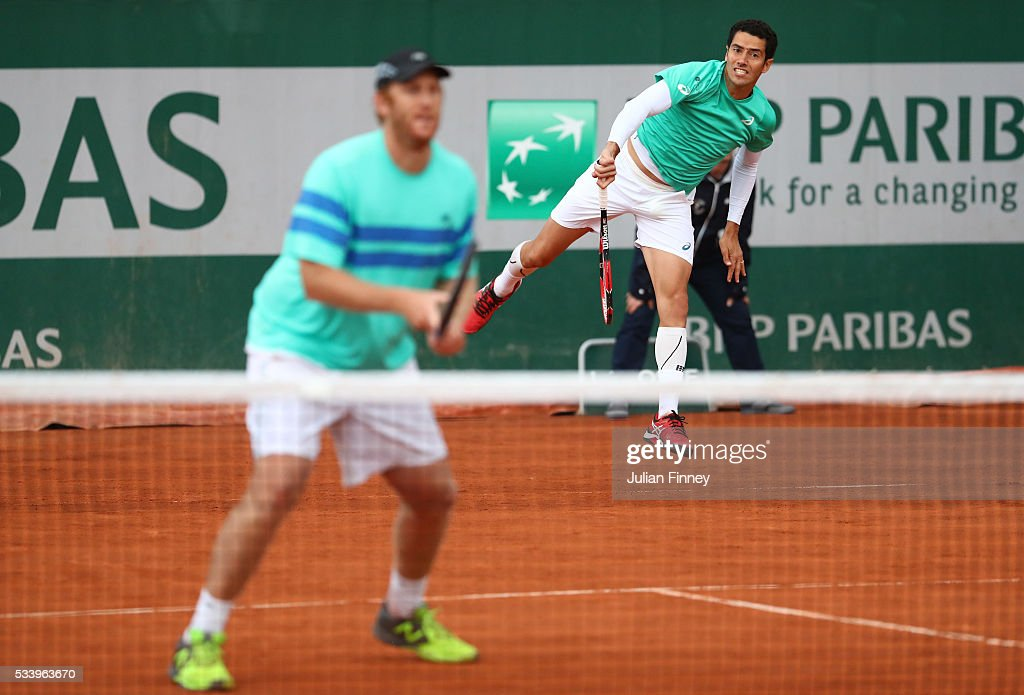 Andre Sa of Brazil serves past Chris Guccione of Australia during the Men's Singles first round match against Juan Sebastian Cabal and Robert Farah of Columbia on day three of the 2016 French Open at Roland Garros on May 24, 2016 in Paris, France.