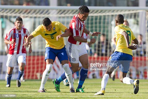 Andre Santos and Ramires of Brazil struggle for the ball with Lucas Barrios of Paraguay during a match as part of Group B of Copa America 2011 at the...