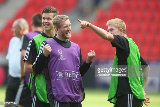Andre Schuerrle of Chelsea smiles with his team mates Marco van Ginkel and Kevin de Bruyne during a training session prior the UEFA Super Cup finale...