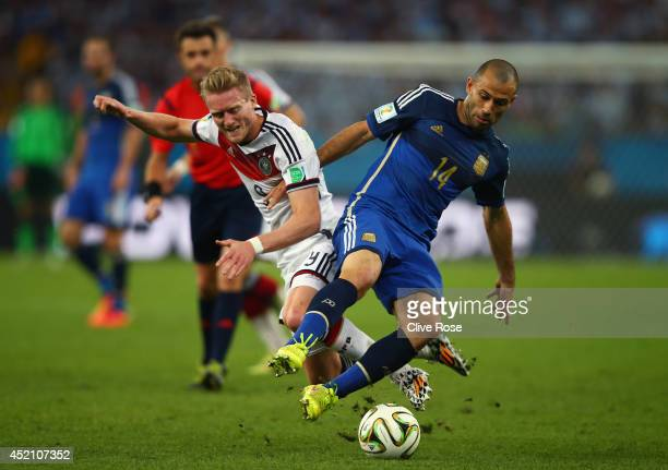 Andre Schuerrle of Germany and Javier Mascherano of Argentina compete for the ball during the 2014 FIFA World Cup Brazil Final match between Germany...