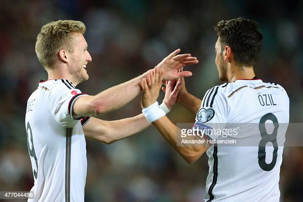 Andre Schuerrle of Germany celebrates scoring the 6th goal with his team mate Mesut Oezil during the UEFA EURO 2016 Qualifier Group D match between...