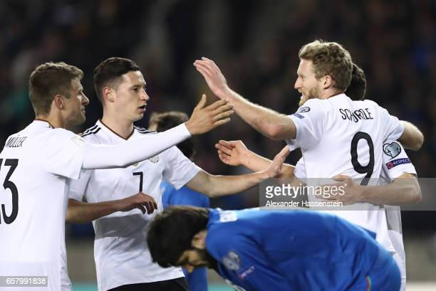 Andre Schuerrle of Germany celebrates scoring the first goal with Julian Draxler and Thomas Mueller during the FIFA 2018 World Cup Qualifing Group C...