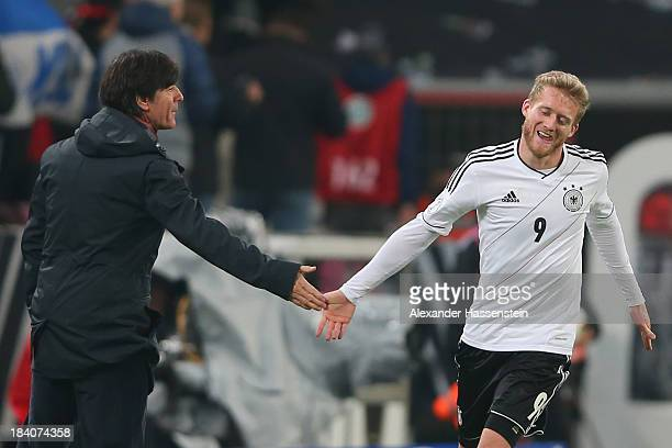 Andre Schuerrle of Germany celebrates scoring the second team goal with his head coach Joachim Loew during the FIFA 2014 World Cup Qualifier Group C...