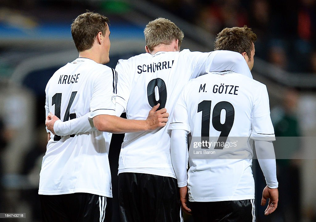 Andre Schuerrle of Germany celebrates with team mates Max Kruse and Mario Goetze after scoring his teams fourth goal during the FIFA 2014 World Cup Qualifying Group C match between Sweden and Germany at Friends Arena Solna on October 15, 2013 in Stockholm, Sweden.