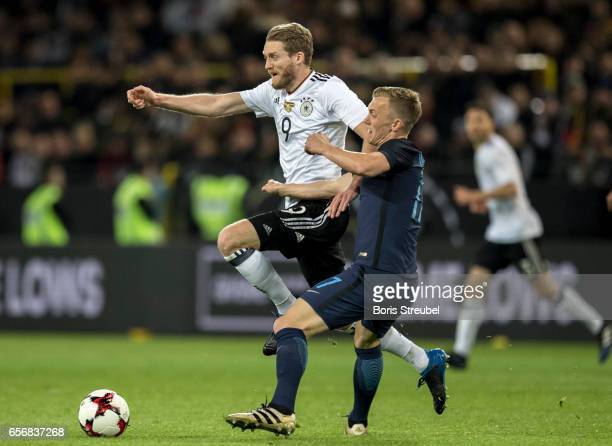 Andre Schuerrle of Germany is challenged by James WardProwse of England during the international friendly match between Germany and England at Signal...