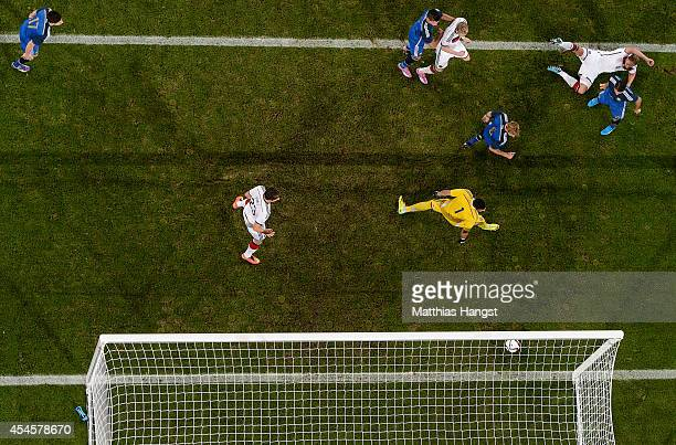 Andre Schuerrle of Germany scores his team's first goal against goalkeeper Sergio Romero of Argentina during the international friendly match between...