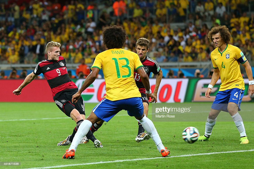 <a gi-track='captionPersonalityLinkClicked' href=/galleries/search?phrase=Andre+Schuerrle&family=editorial&specificpeople=5513825 ng-click='$event.stopPropagation()'>Andre Schuerrle</a> of Germany scores his team's sixth goal against Dante (L) and <a gi-track='captionPersonalityLinkClicked' href=/galleries/search?phrase=David+Luiz&family=editorial&specificpeople=4133397 ng-click='$event.stopPropagation()'>David Luiz</a> of Brazil during the 2014 FIFA World Cup Brazil Semi Final match between Brazil and Germany at Estadio Mineirao on July 8, 2014 in Belo Horizonte, Brazil.
