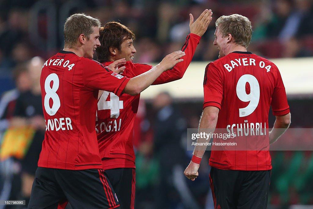 Andre Schuerrle of Leverkusen celebrates scoring the third team goal with his team mates Hajime Hosogai and Lars Bender during the Bundesliga match...