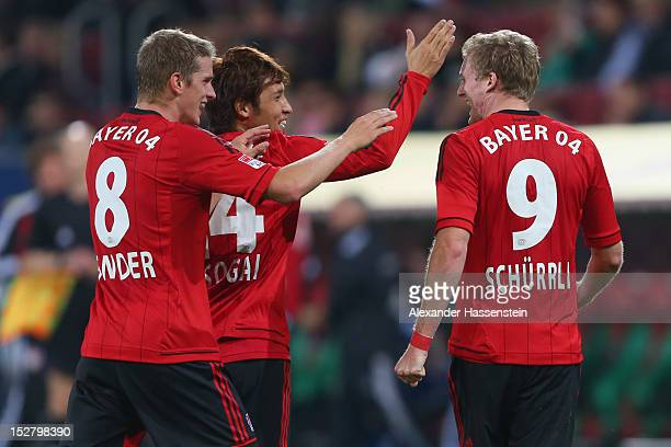 Andre Schuerrle of Leverkusen celebrates scoring the third team goal with his team mates Hajime Hosogai and Lars Bender during the Bundesliga match...