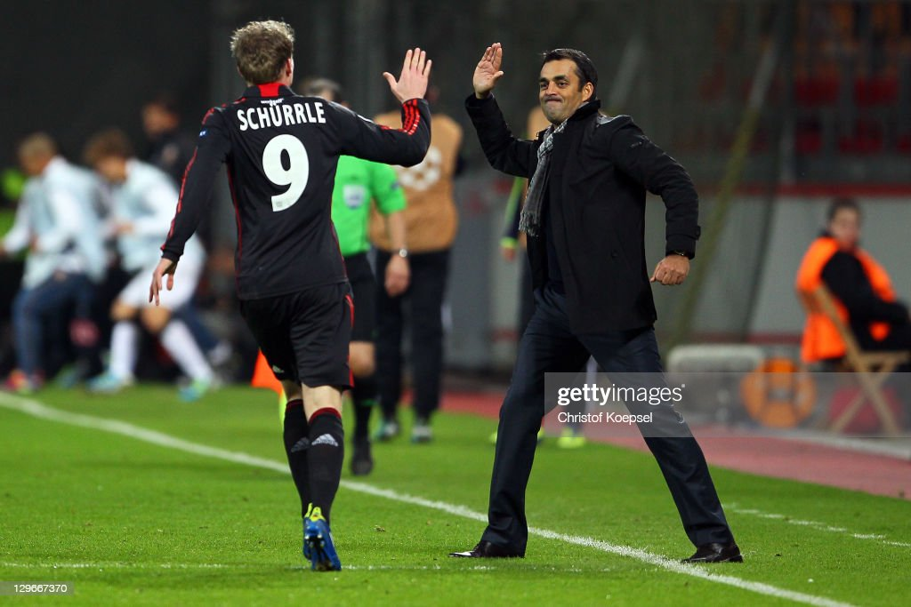 Andre Schuerrle of Leverkusen celebrates the first goalwith head coach Robin Dutt of Leverkusen during the UEFA Champions League group E match...