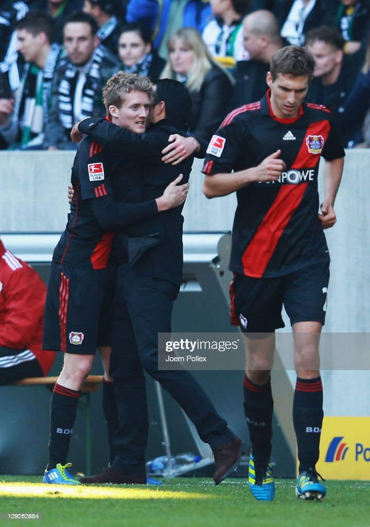 Andre Schuerrle of Leverkusen celebrates with hishead coach Robin Dutt after scoring his team's second goal during the Bundesliga match between...