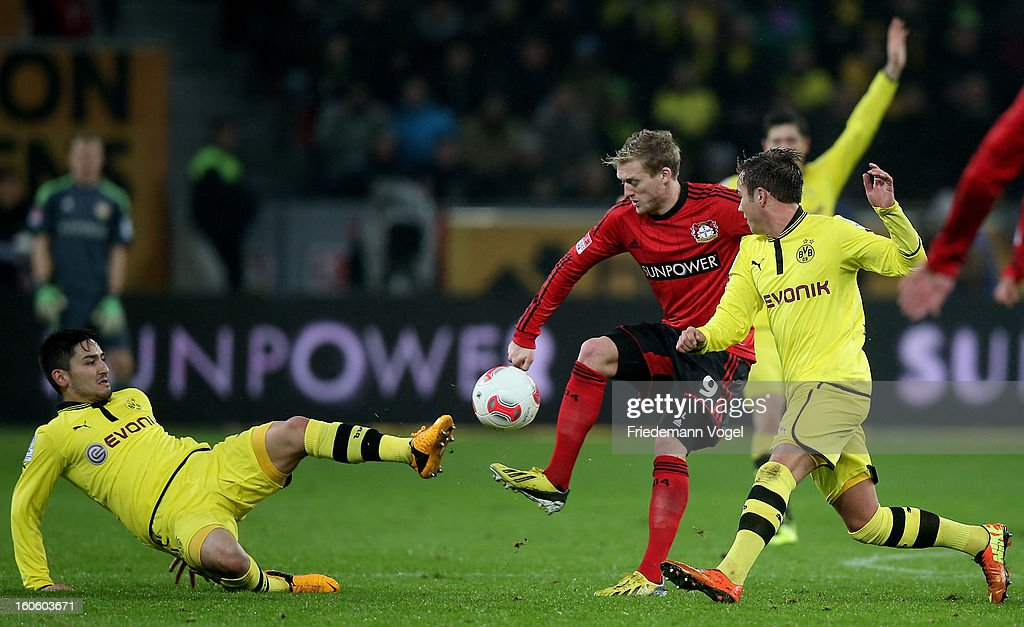 Andre Schuerrle (C) of Leverkusen Ilkay Guendogan (L) and Mario Goetze (R) of Dortmund battle for the ball during the Bundesliga match between Bayer 04 Leverkusen and Borussia Dortmund at BayArena on February 3, 2013 in Leverkusen, Germany.