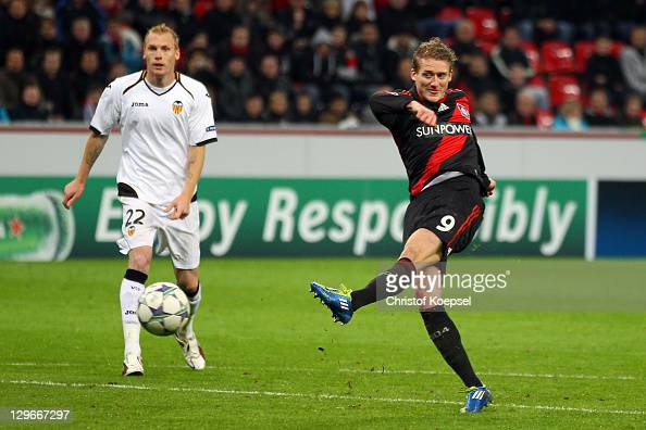 Andre Schuerrle of Leverkusen scores the first goal and Jeremy Mathieu of Valencia watches him during the UEFA Champions League group E match between...