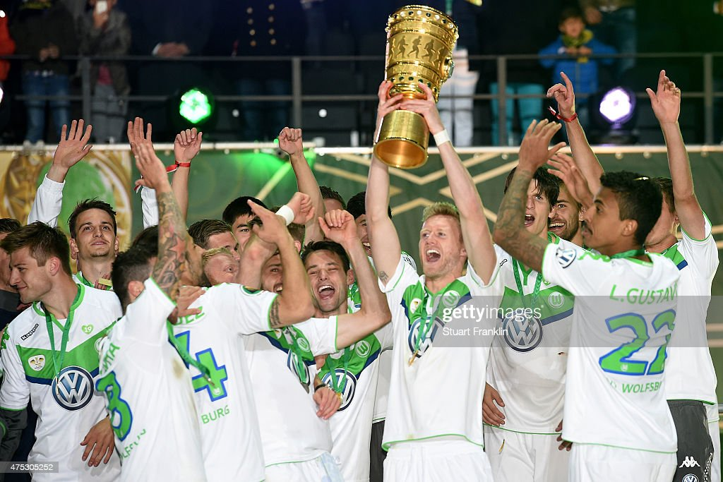 Andre Schuerrle of VfL Wolfsburg lifts the trophy with team mates to celebrate victory after the DFB Cup Final match between Borussia Dortmund and VfL Wolfsburg at Olympiastadion on May 30, 2015 in Berlin, Germany