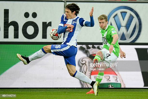 Andre Schuerrle of Wolfsburg is challenged by Nico Schulz of Berlin during the Bundesliga match between VfL Wolfsburg and Hertha BSC Berlin at...
