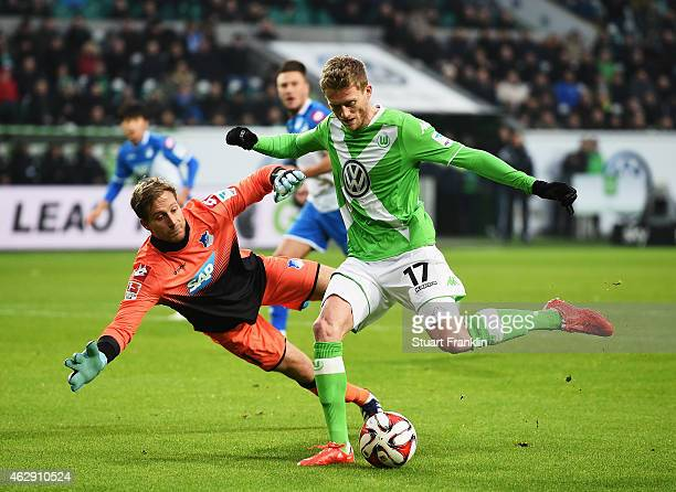 Andre Schuerrle of Wolfsburg is challenged by Oliver Baumann of Hoffenheim during the Bundesliga match between VfL Wolfsburg and 1899 Hoffenheim at...