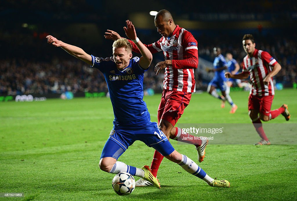 Andre Schurrle of Chelsea goes to ground under a challenge from Miranda of Club Atletico de Madrid during the UEFA Champions League semi-final second leg match between Chelsea and Club Atletico de Madrid at Stamford Bridge on April 30, 2014 in London, England.