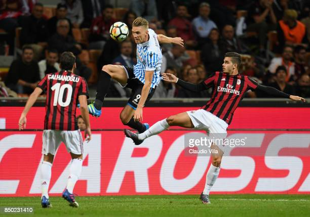 Andre Silva of AC Milan and Bartosz Salamon of Spal compete for the ball during the Serie A match between AC Milan and Spal at Stadio Giuseppe Meazza...