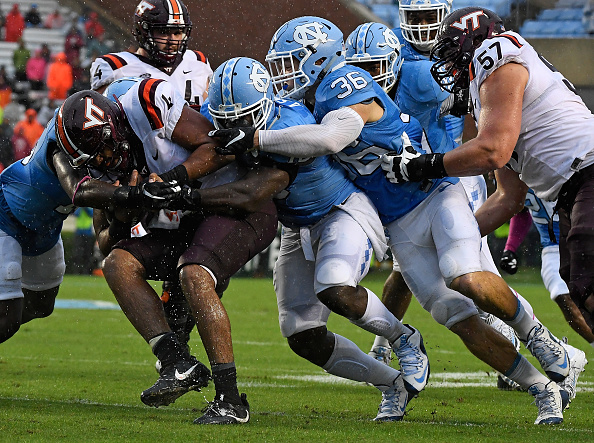 Andre Smith of the UNC Tar Heels leads a tackle of Jerod Evans of the Virginia Tech Hokies at Kenan Stadium on October 8 2016 in Chapel Hill North...