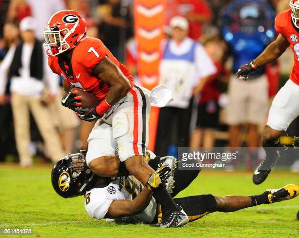 Andre Swift of the Georgia Bulldogs runs over Thomas Wilson of the Missouri Tigers at Sanford Stadium on October 14 2017 in Athens Georgia
