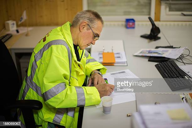 Andre van Krieken a 69yearold employed via specialist seniors recruitment company 65plus fills out a form as he sits in an office while working on...