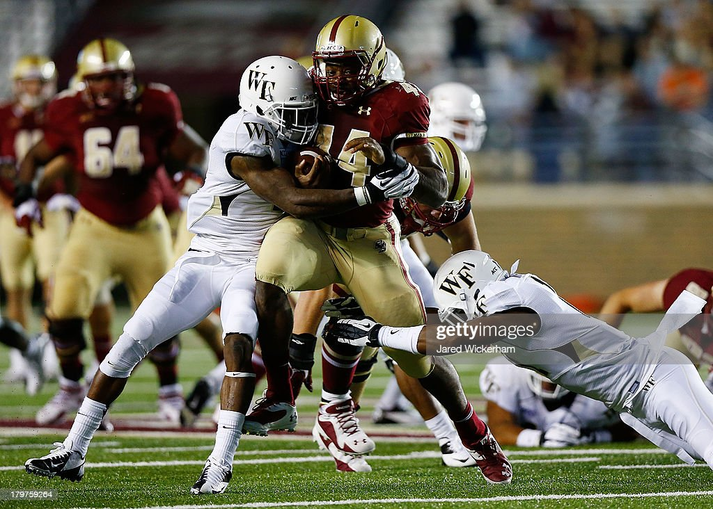 Andre Williams #44 of the Boston College Eagles attempts to run through two Wake Forest Demon Deacons defenders in the second quarter during the game on September 6, 2013 at Alumni Stadium in Chestnut Hill, Massachusetts.