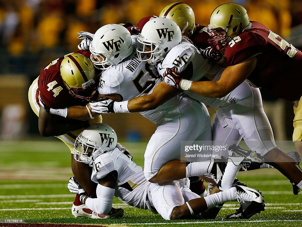 Andre Williams #44 of the Boston College Eagles is tackled by a gang of Wake Forest Demon Deacons defenders in the first quarter during the game on September 6, 2013 at Alumni Stadium in Chestnut Hill, Massachusetts.