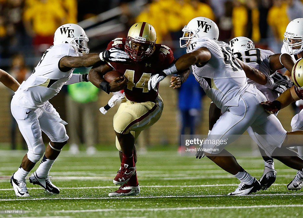 Andre Williams #44 of the Boston College Eagles runs with the ball through a couple of Wake Forest Demon Deacons defenders in the fourth quarter during the game on September 6, 2013 at Alumni Stadium in Chestnut Hill, Massachusetts.