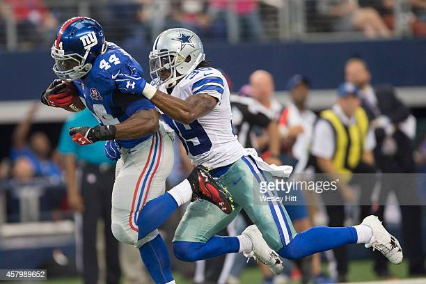 Andre Williams of the New York Giants is hit while running the ball by Brandon Carr of the Dallas Cowboys at ATT Stadium on October 19 2014 in...