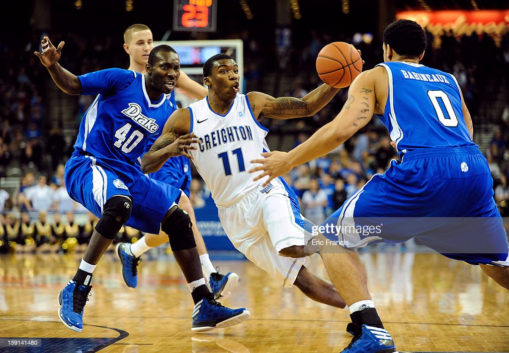Andre Yates #11 of the Creighton Bluejays drives between Daddy Ugbede #40 and Kori Babineaux #0 of the Drake Bulldogs during their game at the CenturyLink Center on January 8, 2013 in Omaha, Nebraska. Creighton defeated Drake 91-61.