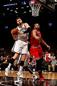 Andrea Bargnani of the Brooklyn Nets pulls in a rebound in front of Joakim Noah of the Chicago Bulls during their game at Barclays Center on October...