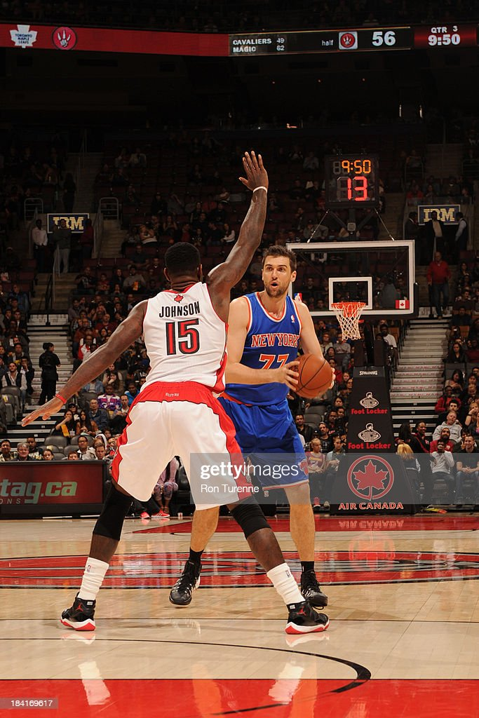 <a gi-track='captionPersonalityLinkClicked' href=/galleries/search?phrase=Andrea+Bargnani&family=editorial&specificpeople=533014 ng-click='$event.stopPropagation()'>Andrea Bargnani</a> #77 of the New York Knicks looks to pass the ball against <a gi-track='captionPersonalityLinkClicked' href=/galleries/search?phrase=Amir+Johnson&family=editorial&specificpeople=556786 ng-click='$event.stopPropagation()'>Amir Johnson</a> #15 of the Toronto Raptors during the game on October 11, 2013 at the Air Canada Centre in Toronto, Ontario, Canada.