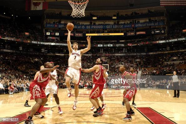 Andrea Bargnani of the Toronto Raptors drives the lane and looks to sink the onehanded jumper next to Luis Scola of the Houston Rockets during a game...