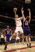 Andrea Bargnani of the Toronto Raptors drives to the net with the fingerroll past Pau Gasol of the Los Angeles Lakers during a game on January 24...
