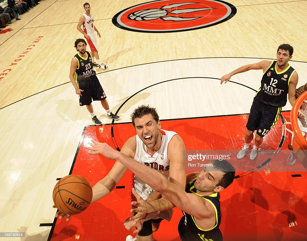 <a gi-track='captionPersonalityLinkClicked' href=/galleries/search?phrase=Andrea+Bargnani&family=editorial&specificpeople=533014 ng-click='$event.stopPropagation()'>Andrea Bargnani</a> #7 of the Toronto Raptors goes to the basket under pressure during the game between the Real Madrid and the Toronto Raptors on October 8, 2012 at the Air Canada Centre in Toronto, Canada.