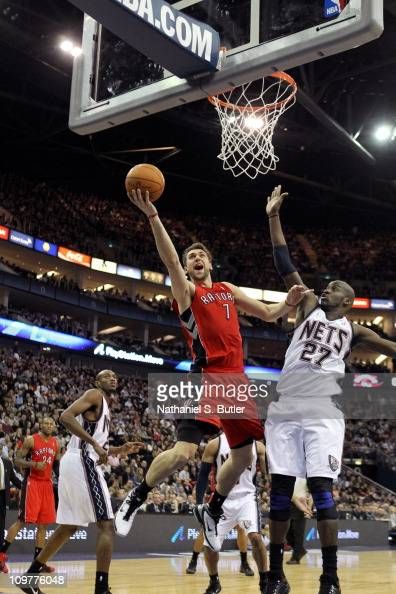 Andrea Bargnani of the Toronto Raptors shoots against Johan Petro of the New Jersey Nets during their game at the O2 Arena on March 4 2011 in London...