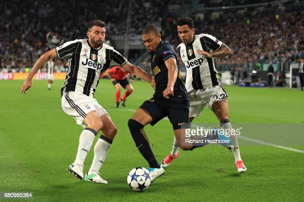 Andrea Barzagli and Dani Alves of Juventus close down Kylian Mbappe of AS Monaco during the UEFA Champions League Semi Final second leg match between...
