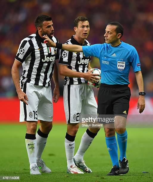 Andrea Barzagli and Stephan Lichtsteiner of Juventus talk to referee Cuneyt Cakir during the UEFA Champions League Final between Juventus and FC...