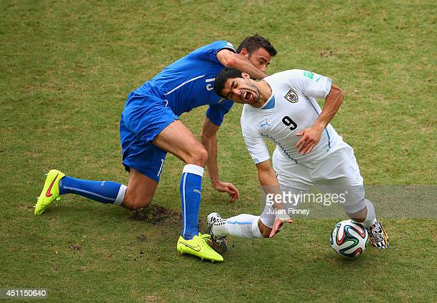 Andrea Barzagli of Italy challenges Luis Suarez of Uruguay during the 2014 FIFA World Cup Brazil Group D match between Italy and Uruguay at Estadio...