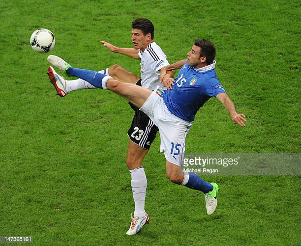 Andrea Barzagli of Italy challenges Mario Gomez of Germany during the UEFA EURO 2012 semi final match between Germany and Italy at National Stadium...