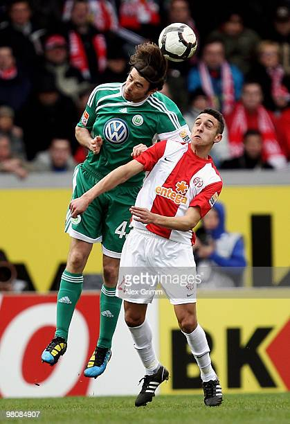 Andrea Barzagli of Wolfsburg jumps for a header with Chadli Amri of Mainz during the Bundesliga match between FSV Mainz 05 and VfL Wolfsburg at the...