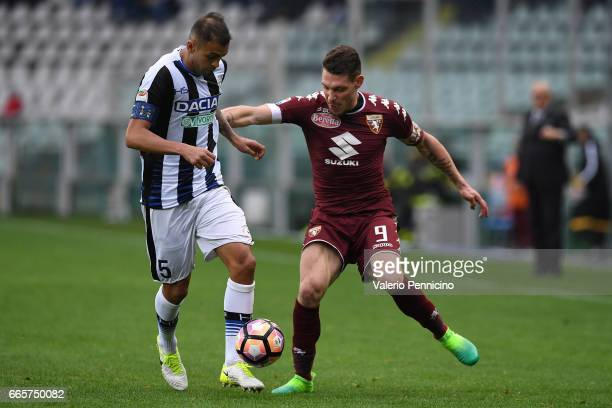 Andrea Belotti of FC Torino is challenged by Larangeira Danilo of Udinese Calcio during the Serie A match between FC Torino and Udinese Calcio at...