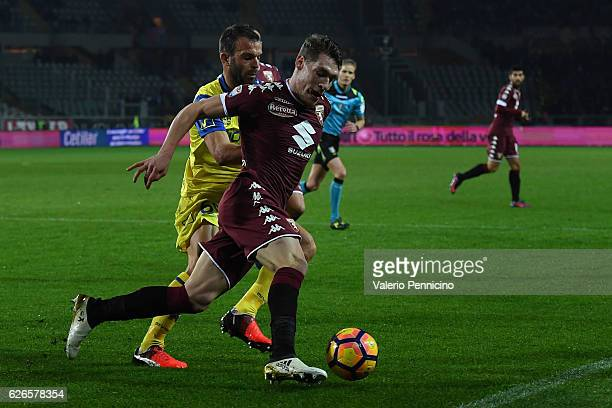 Andrea Belotti of FC Torino is challenged by Riccardo Meggiorini of AC ChievoVerona during the Serie A match between FC Torino and AC ChievoVerona at...