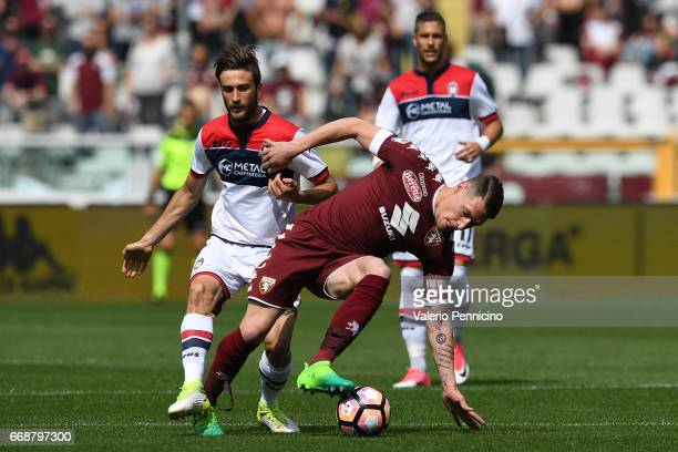 Andrea Belotti of FC Torino is tackled by Adrian Marius Stoian of FC Crotone during the Serie A match between FC Torino and FC Crotone at Stadio...