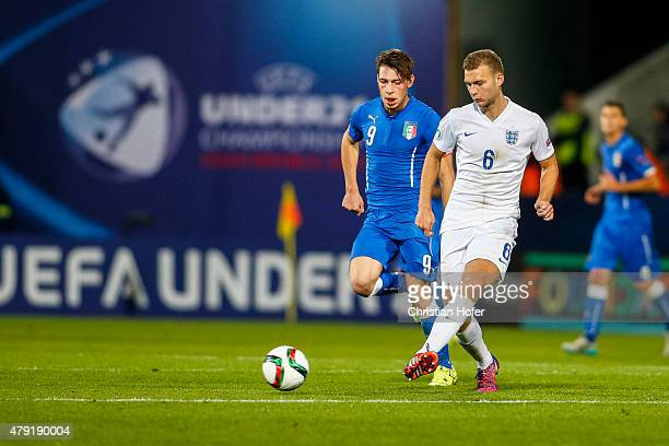 Andrea Belotti of Italy competes for the ball with Ben Gibson of England during the UEFA Under21 European Championship 2015 match between England and...