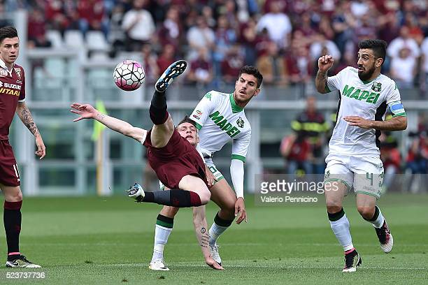 Andrea Belotti of Torino FC competes is tackled by Lorenzo Pellegrini of US Sassuolo Calcio during the Serie A match between Torino FC and US...