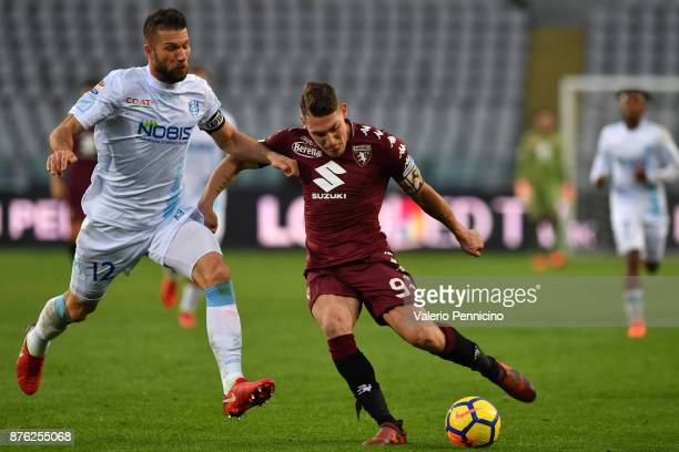 Andrea Belotti of Torino FC is challenged by Bostjan Cesar of AC Chievo Verona during the Serie A match between Torino FC and AC Chievo Verona at...